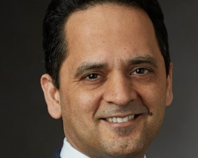 Sandeep Dadlani wearing a suit and tie smiling at the camera